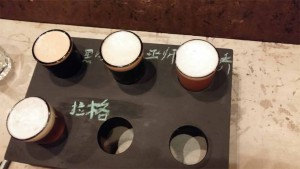 "Clockwise from top left: Back in Black Stout 回归黑暗; Heart of Darkness Belgian Bruin 巫师; Blonde on Blonde Belgian Ale 二乔; Two Birds Helles 一箭双雕 (marked ""lager"" 拉格)"